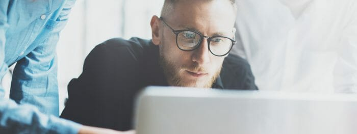 man in glasses looking at computer
